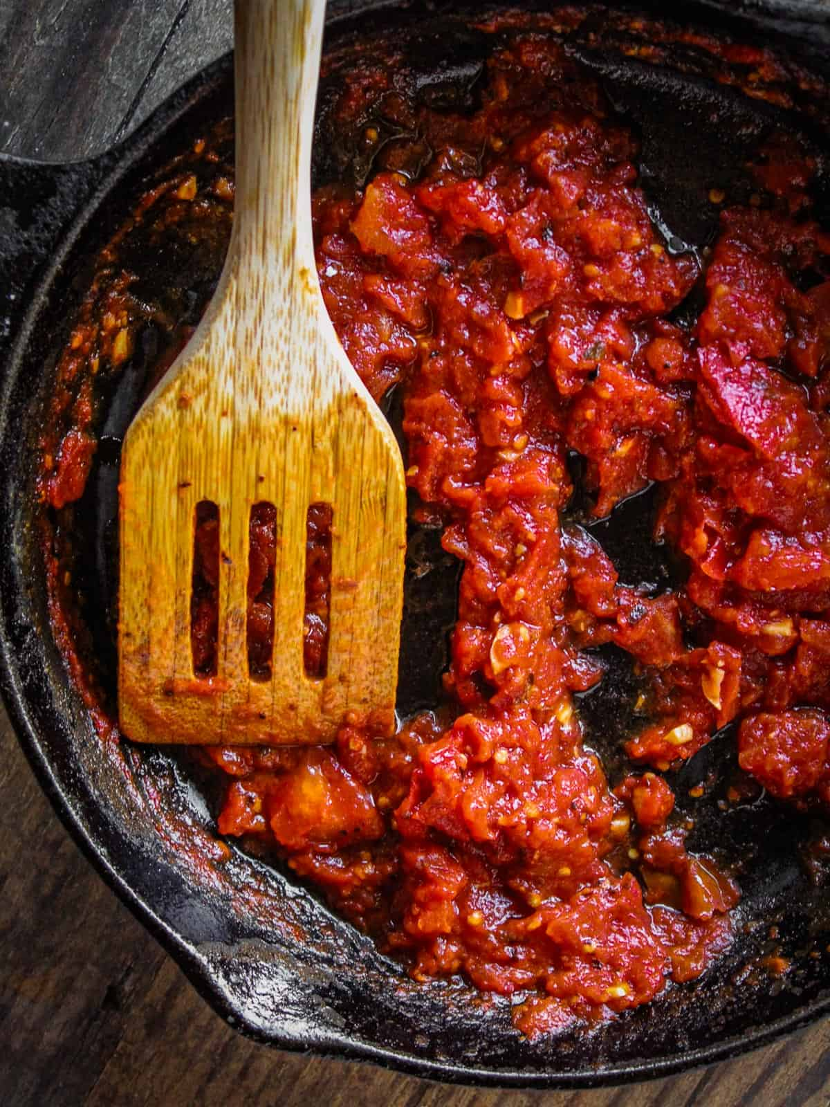 arrabiata dip in a cast iron skillet with a wooden spatula