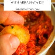 hand dipping fried goat cheese in arrabiata dip