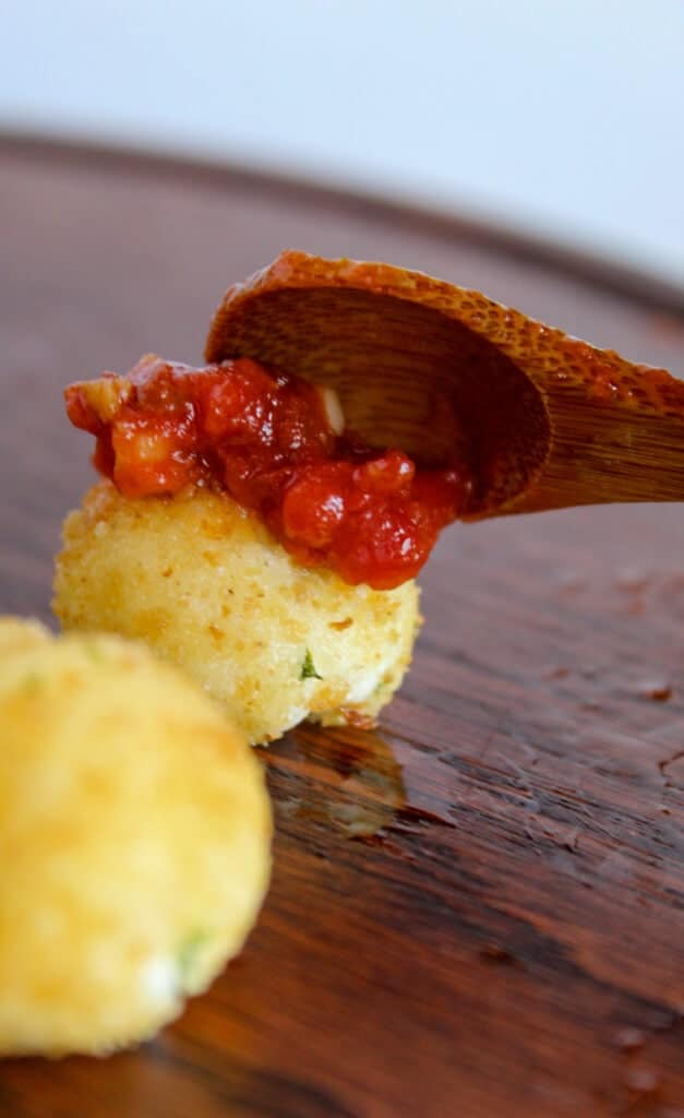 tiny wooden spoon placing red sauce on goat cheese