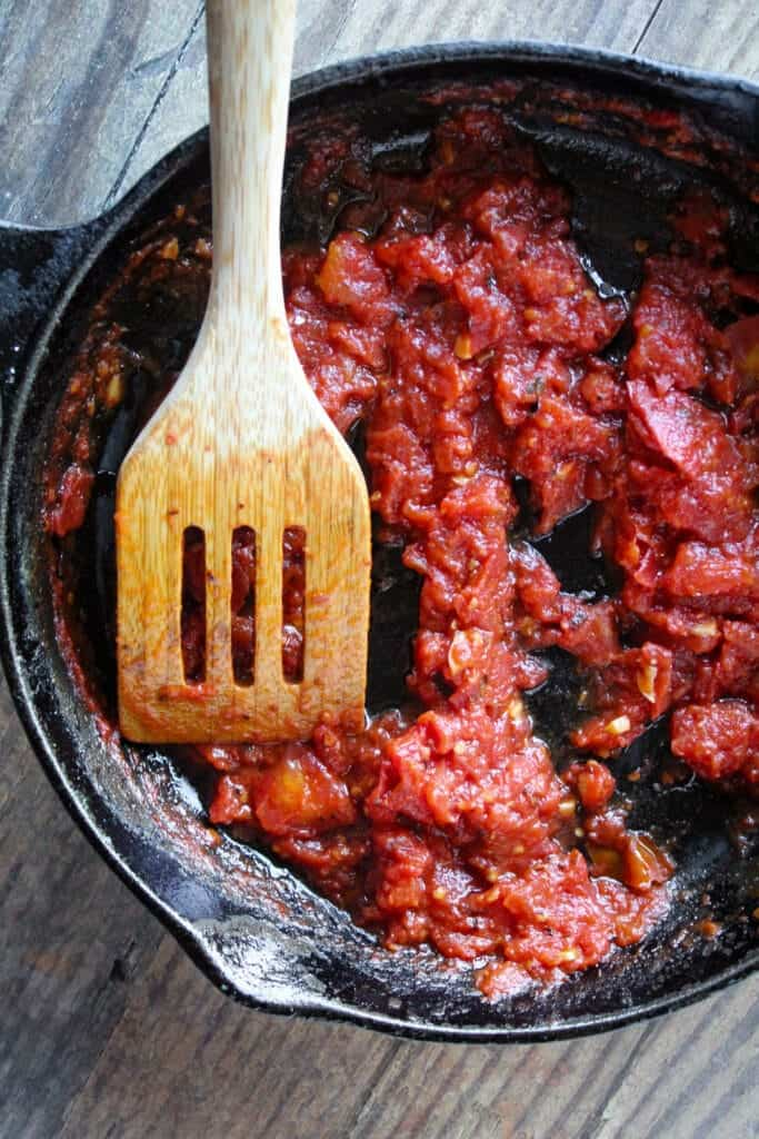 black cast iron pan with thick arrabbiata dip in it with a wooden spatula on the side