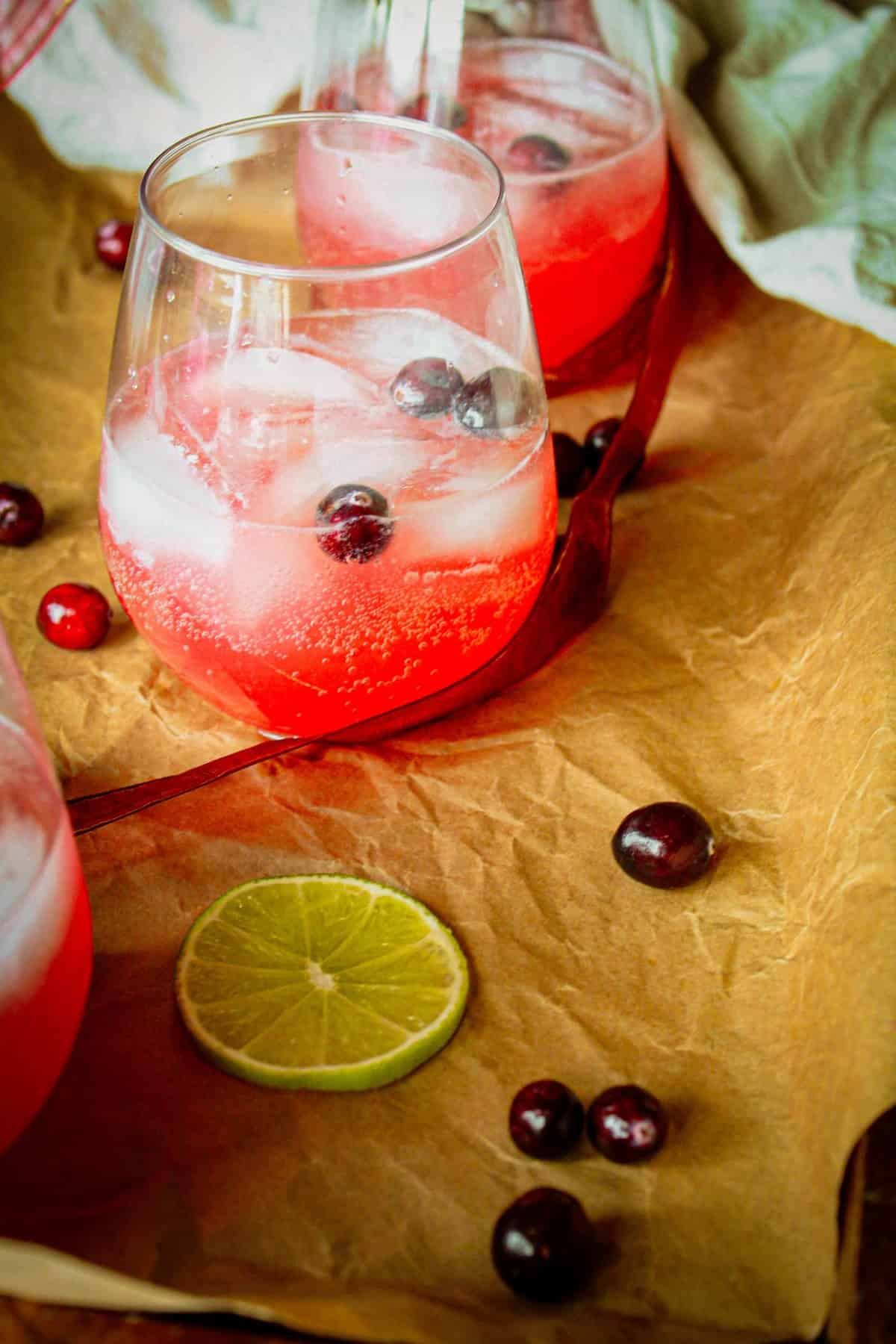 two cocktails on a tray with parchment paper and fresh cranberries lying next to it