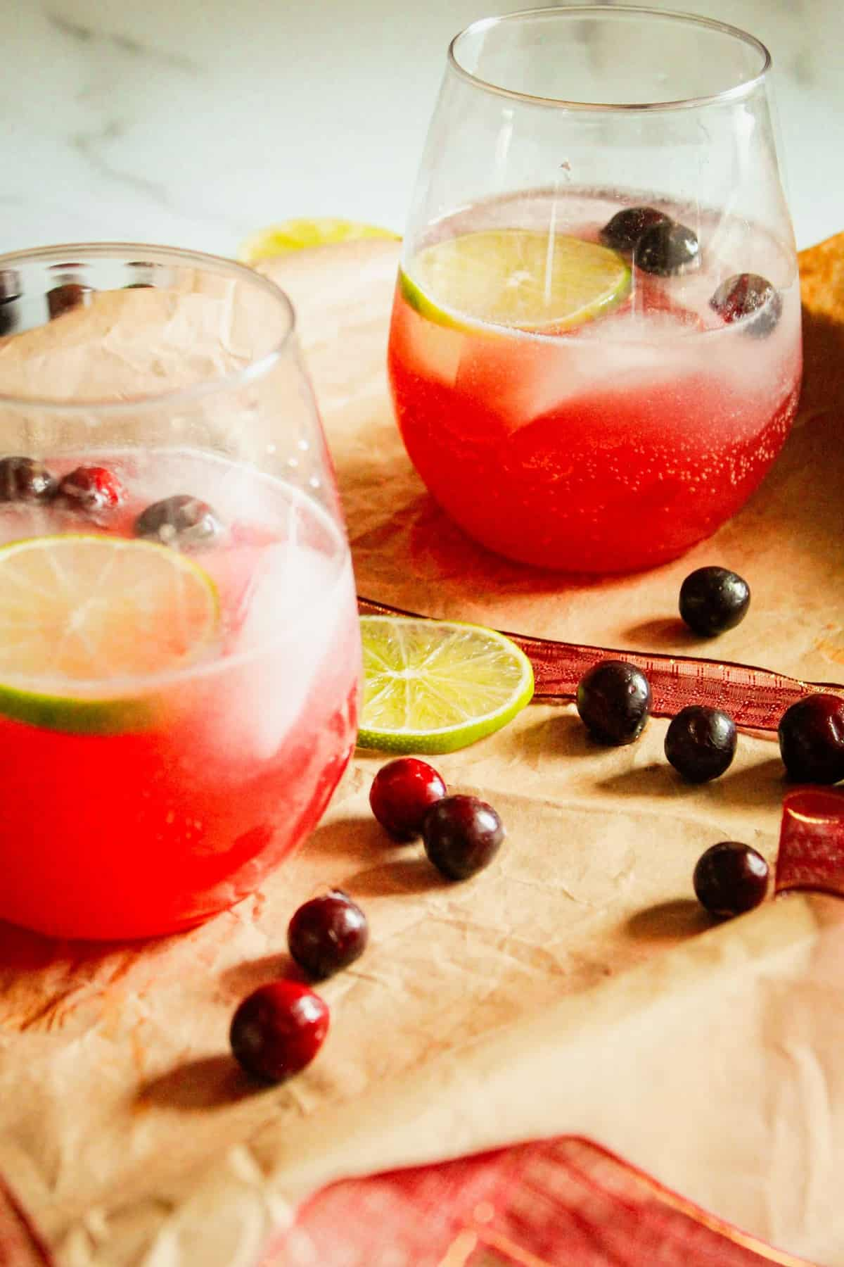 cranberry moscow mule cocktails on a tray with fresh cranberries and red holiday ribbon