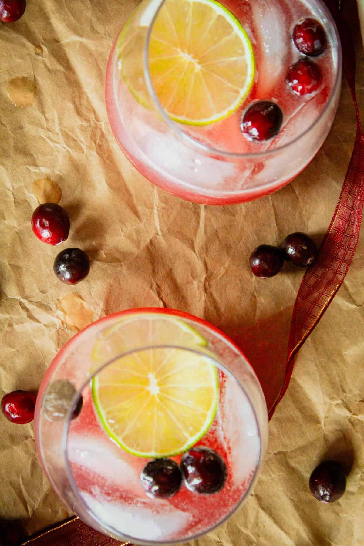 overhead shot of two wine glasses with a cranberry christmas moscow mule