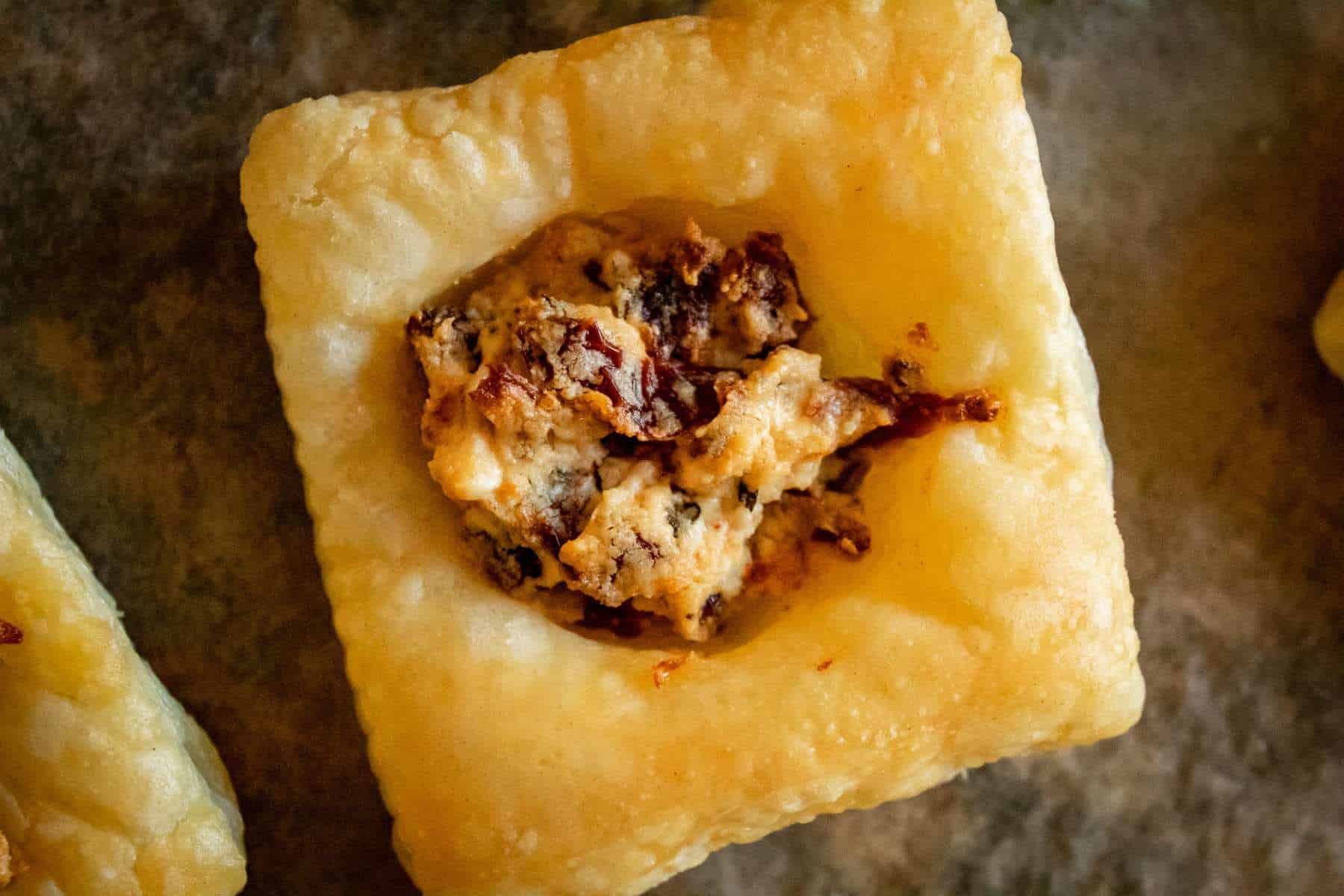 close up of a square puff pastry appetizer filled with a goat cheese and sundried tomato mixture