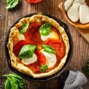 pizza in a cast iron skillet with tomatoes, cheese and fresh basil