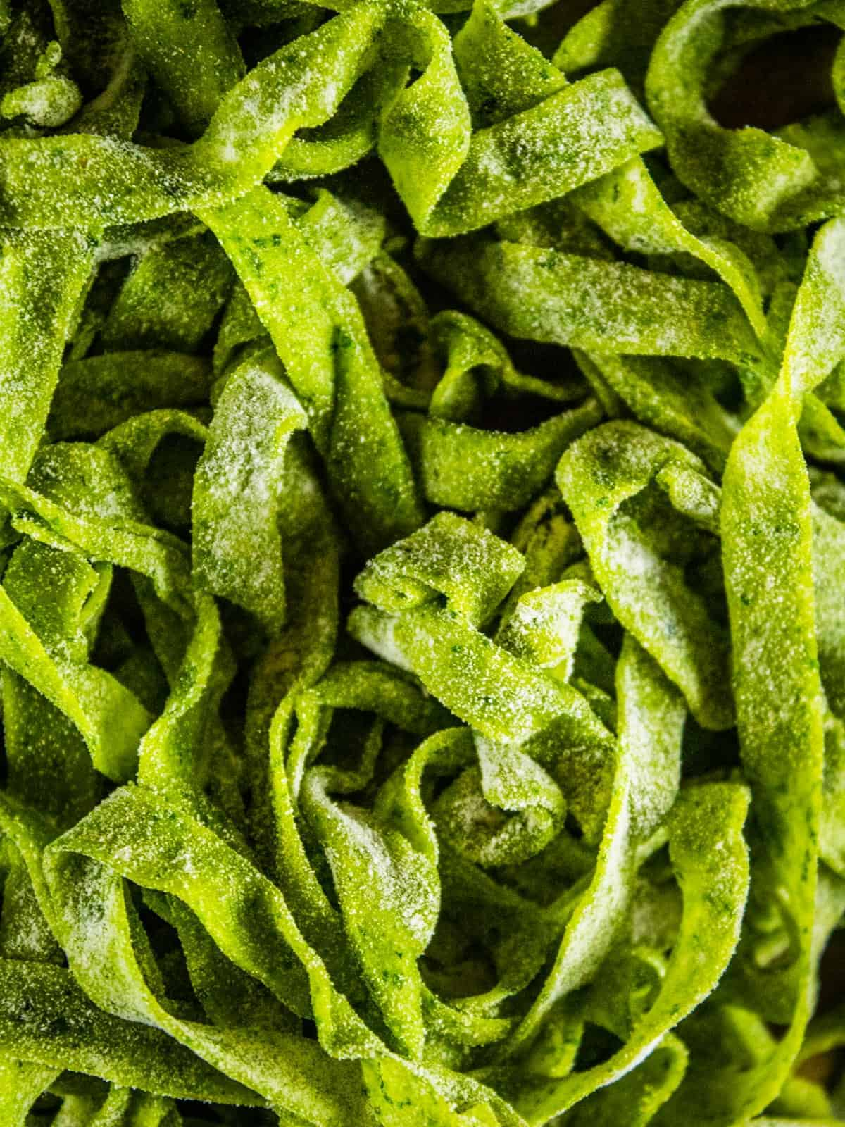 close up fresh spinach fettuccine noodles tossed with flour