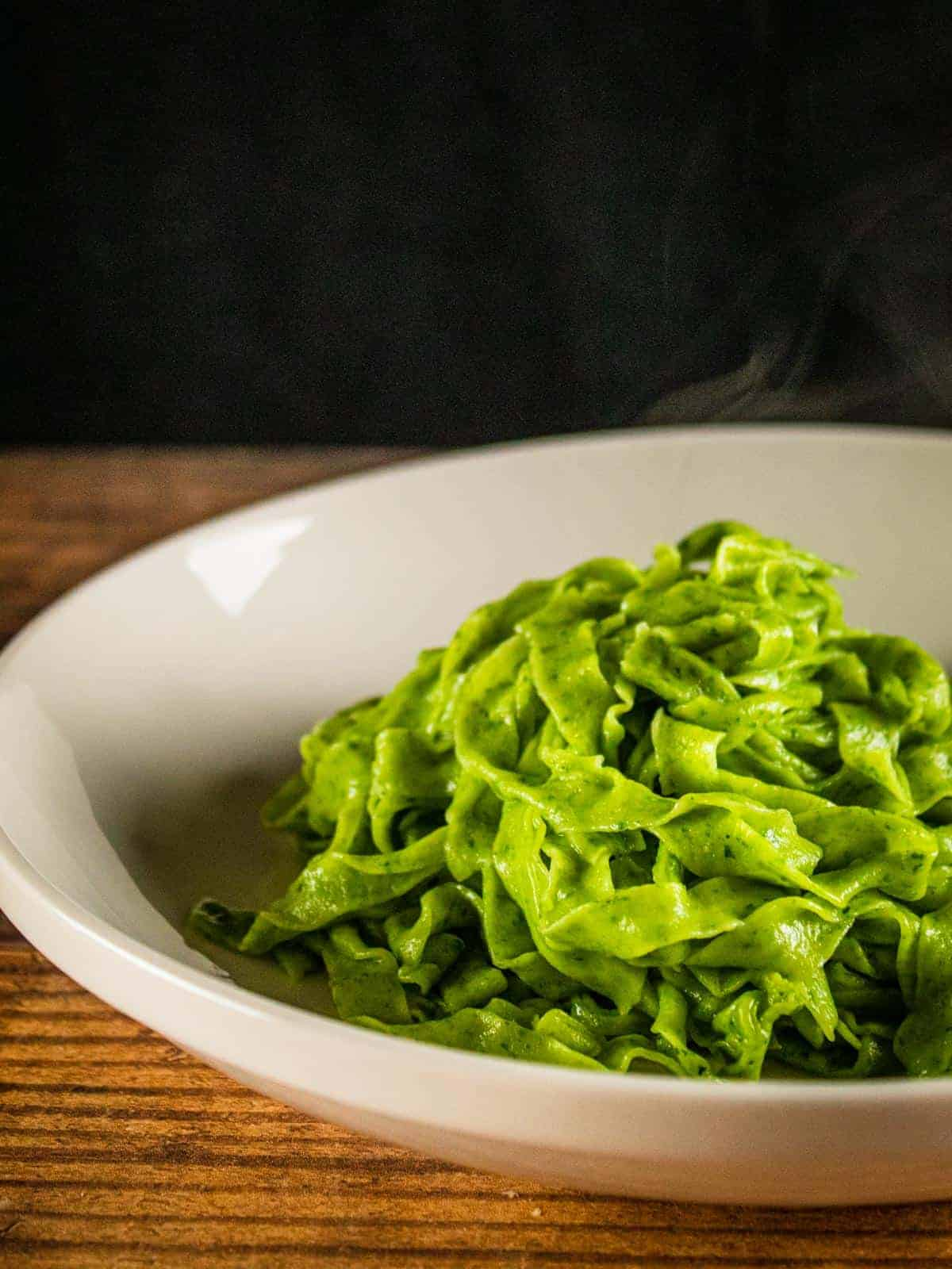 cooked spinach fettuccine on a white plate