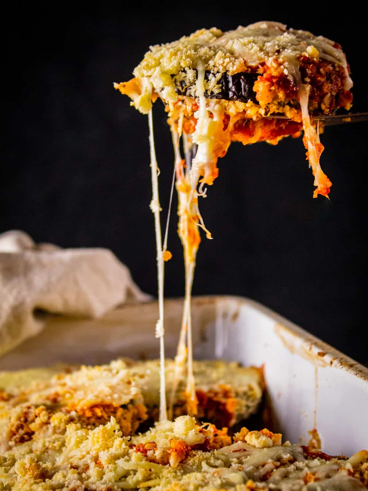 eggplant slice on a serving spatula with cheese pulling from it