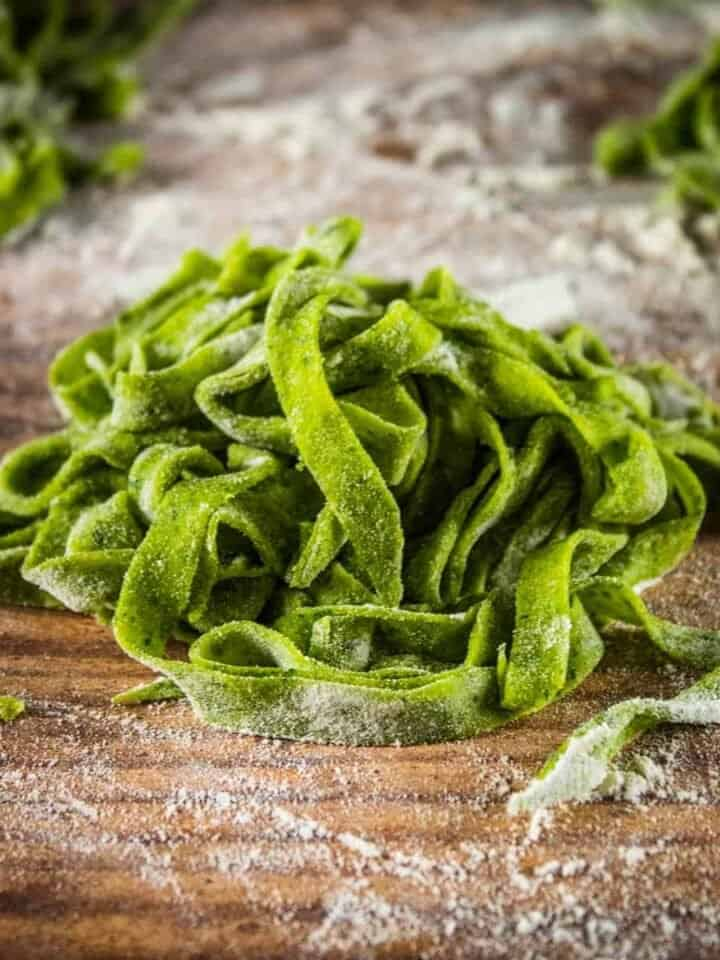 pile of uncooked homemade spinach fettuccine on a table
