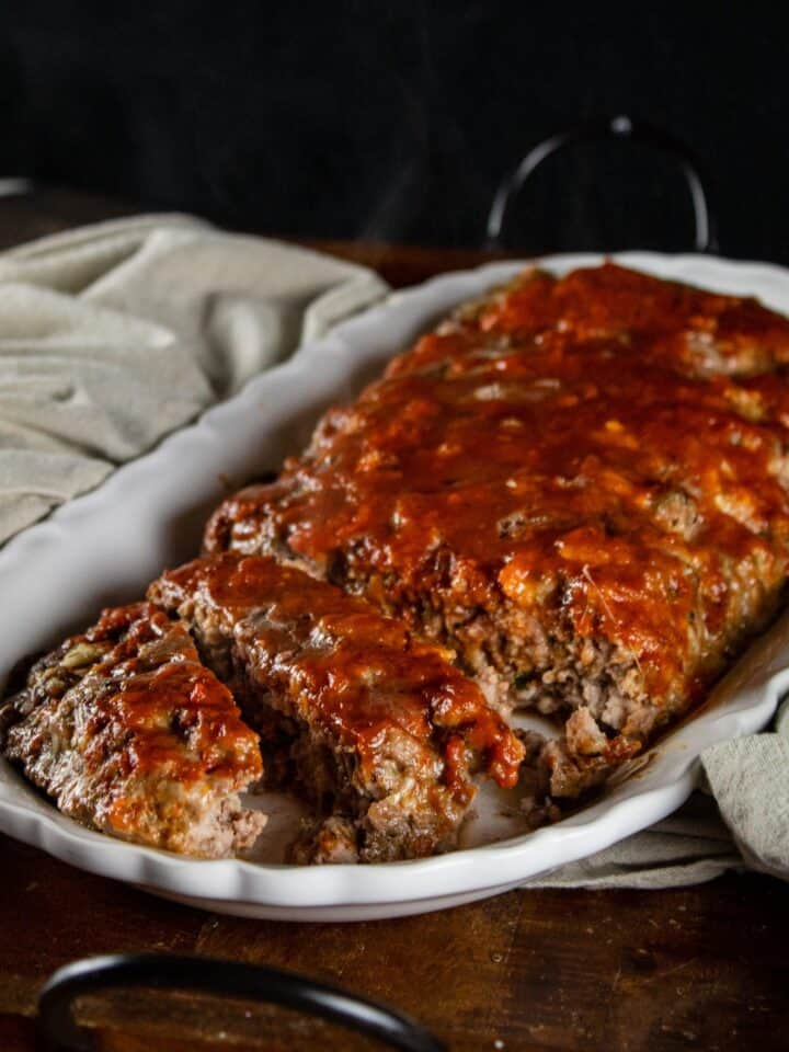 italian meatloaf with marainara on top of it on a white serving platter