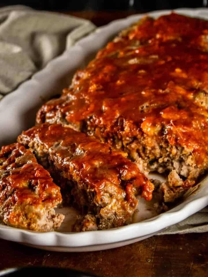 partially sliced italian meatloaf on a white platter