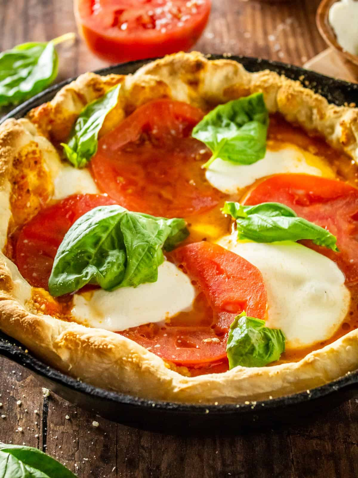 cast iron pizza with tomatoes, mozzarella and fresh basil
