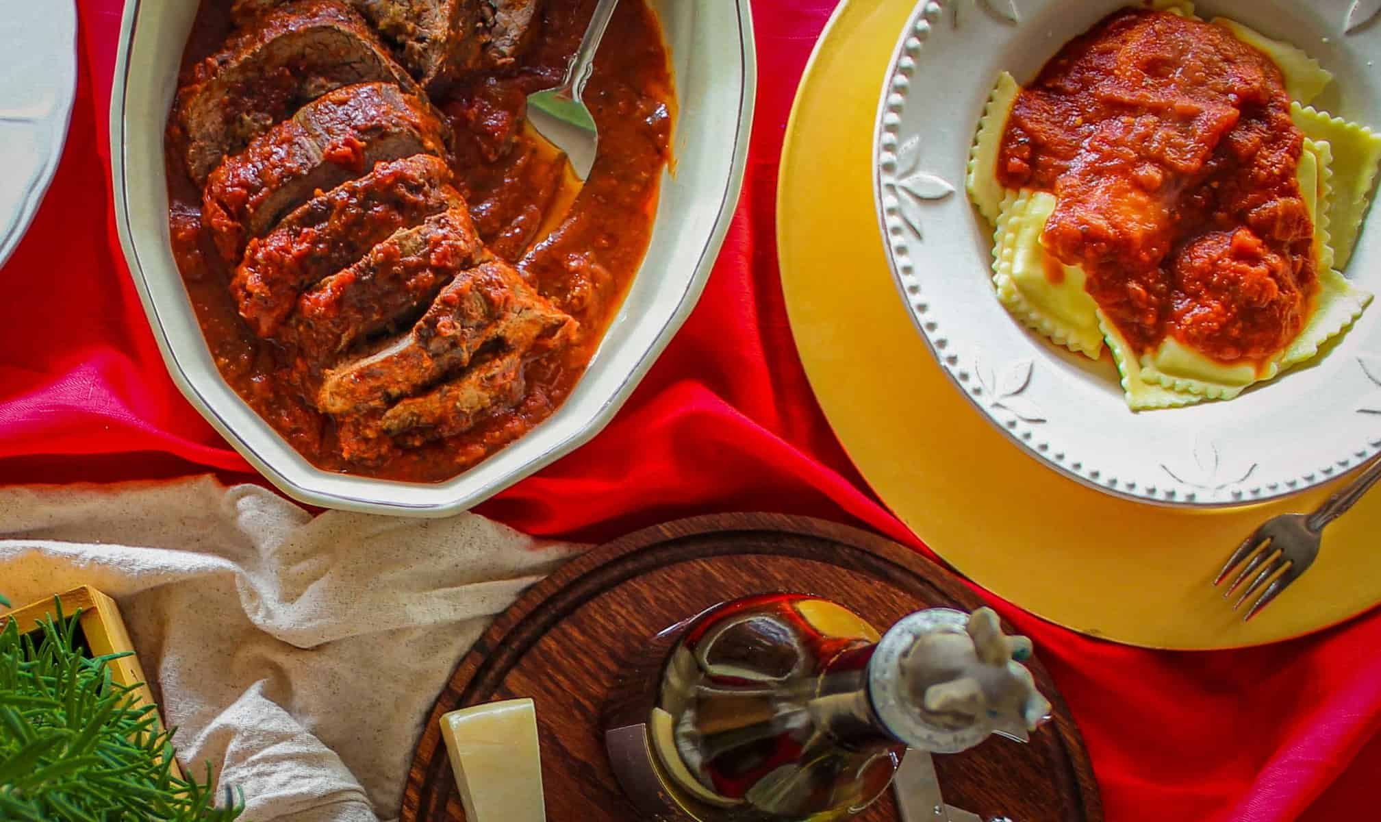 overhead shot of a dinner table with braciole and ravioli with marinara