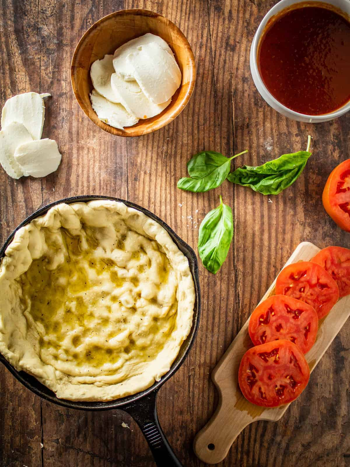 cast iron pizza crust next to cheese, tomatoes and basil