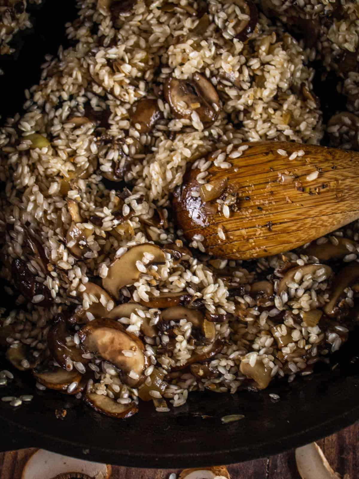 wooden spoon stirring rice and mushrooms