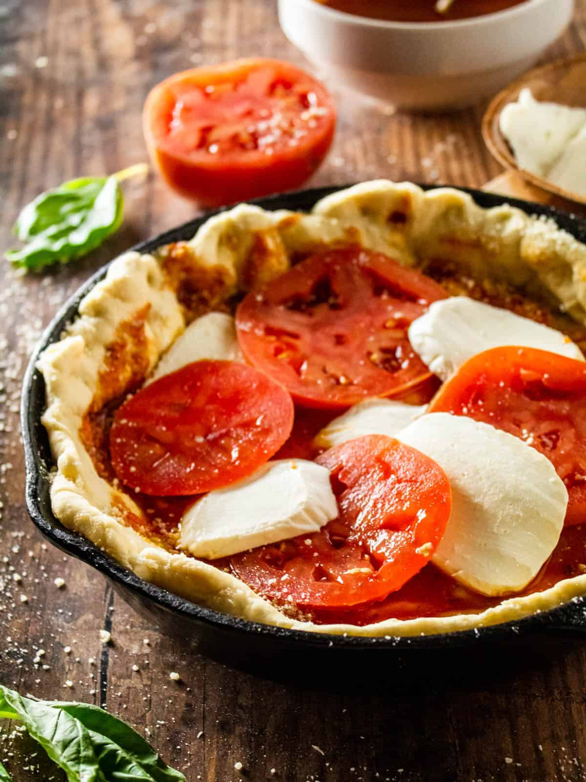 sliced fresh mozzarella and tomatoes with marinara on pizza dough in a skillet