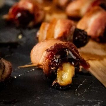 bacon wrapped dates filled with cheese on a slate and wooden tray with a toothpick in it