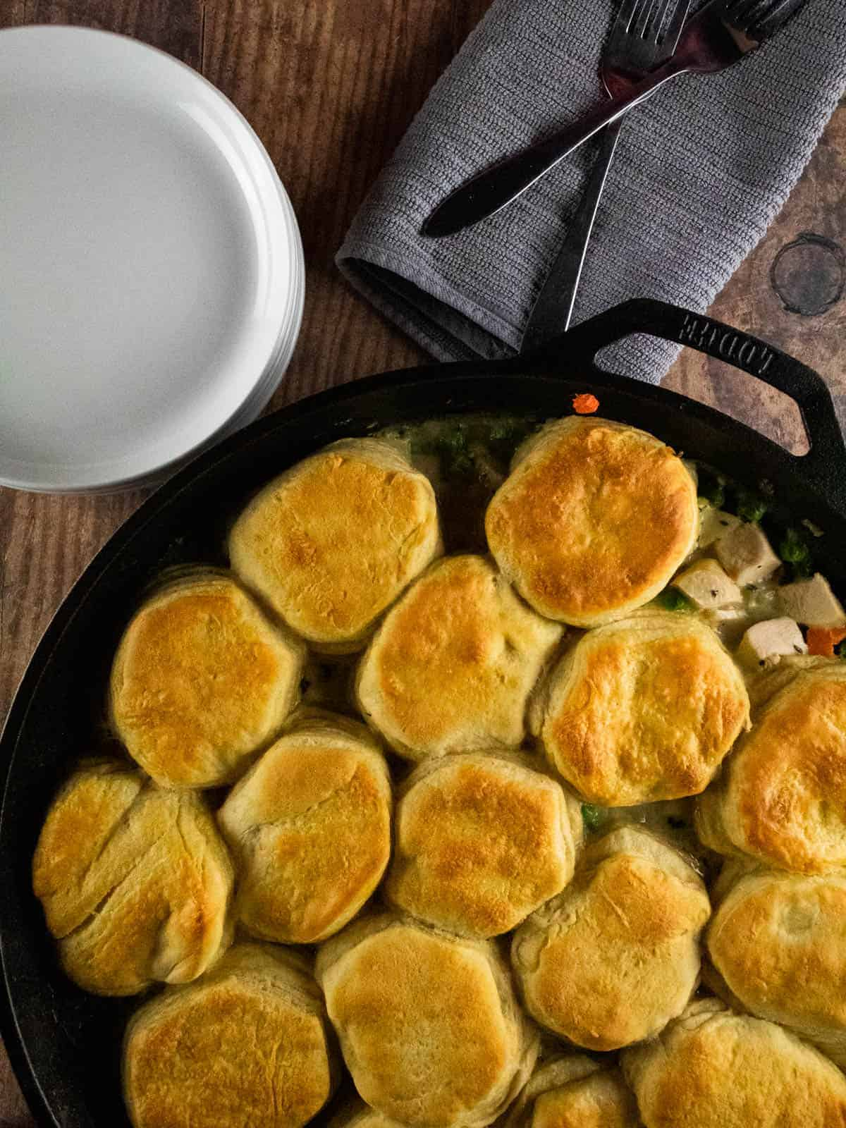 cast iron skillet of cooked chicken pot pie with biscuits