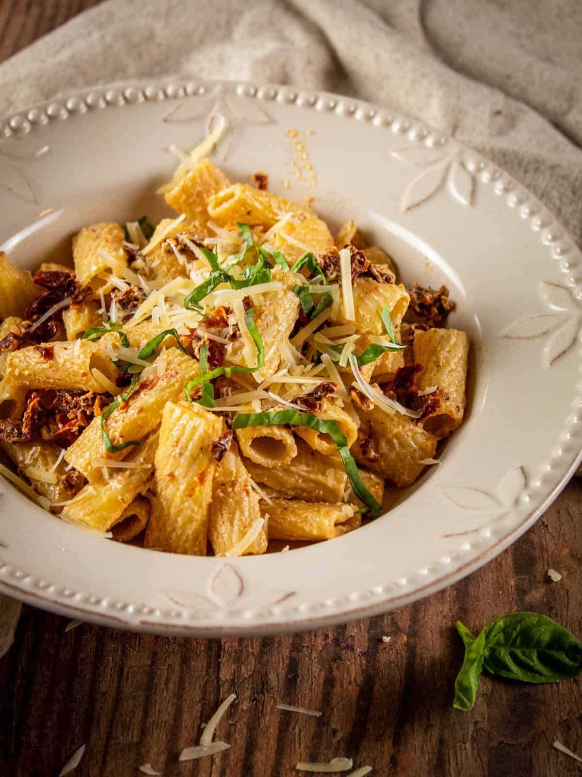 bowl of rigatoni pasta with sundried tomatoes and fresh basil