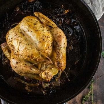 roasted whole trussed chicken in a large cast iron skillet