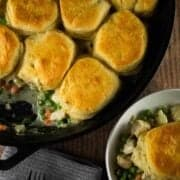 pot pie topped with biscuits in a cast irion skillet