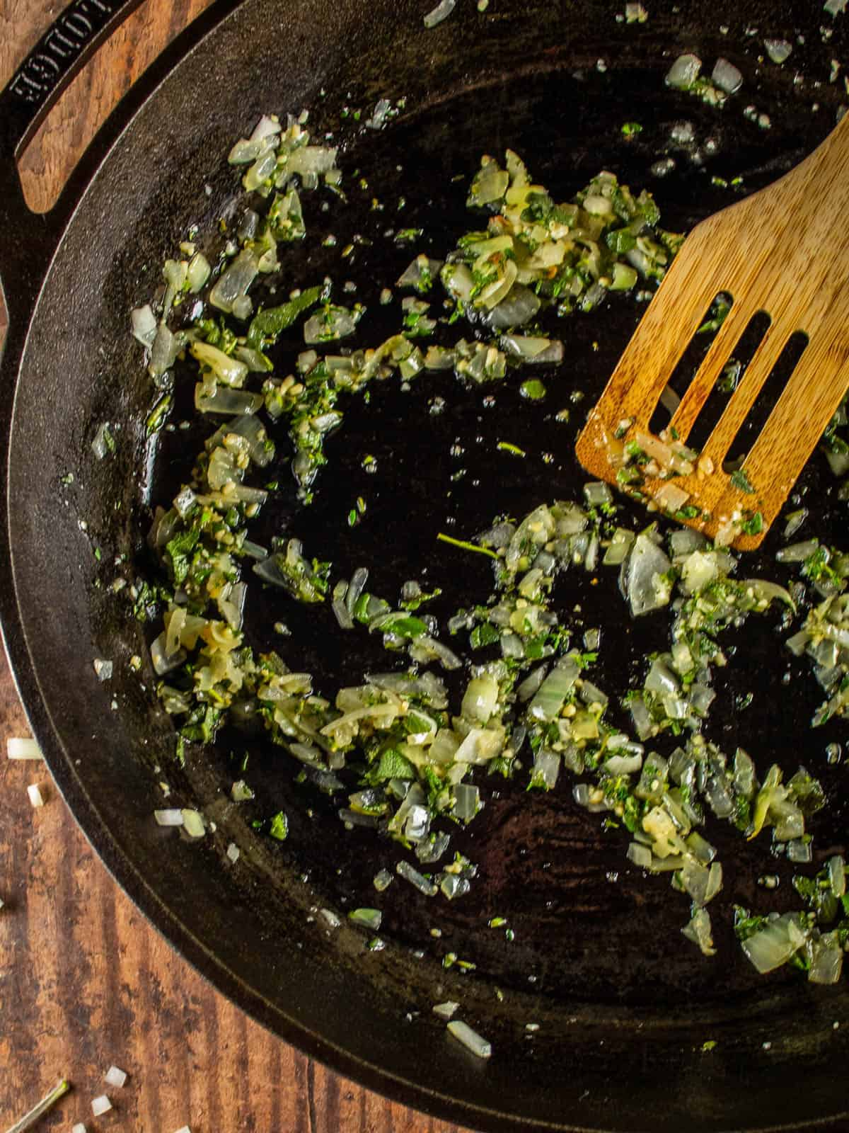 wooden spatula stirring herbs and onions in a cast iron skillet