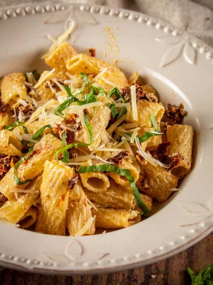 bowl of rigatoni with sundried tomatoes and fresh basil