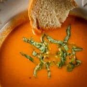 bowl of creamy tomato soup with fresh basil and italian bread