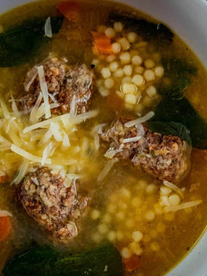 bowl of italian wedding soup with parmesan on top