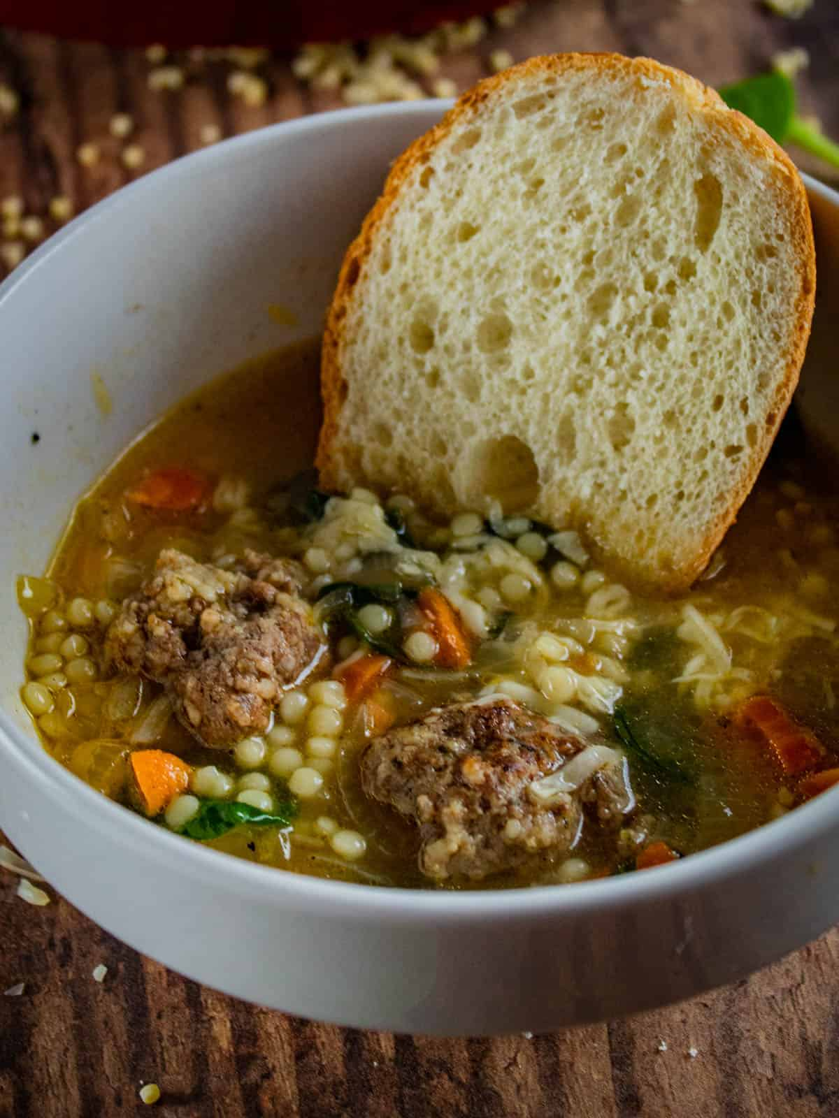 fresh bread in a bowl of italian wedding soup