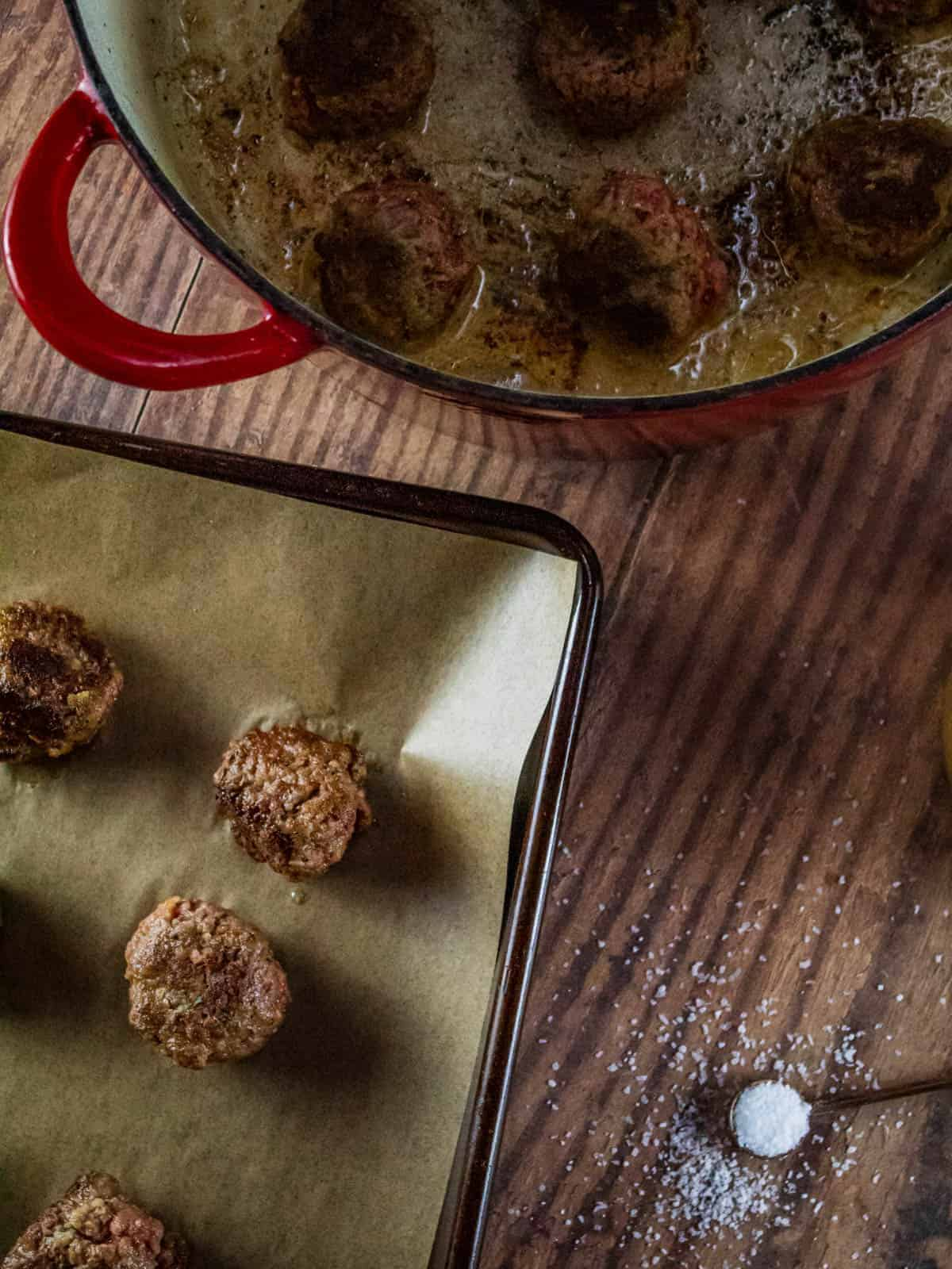 browned meatballs in a pot and on a sheet pan