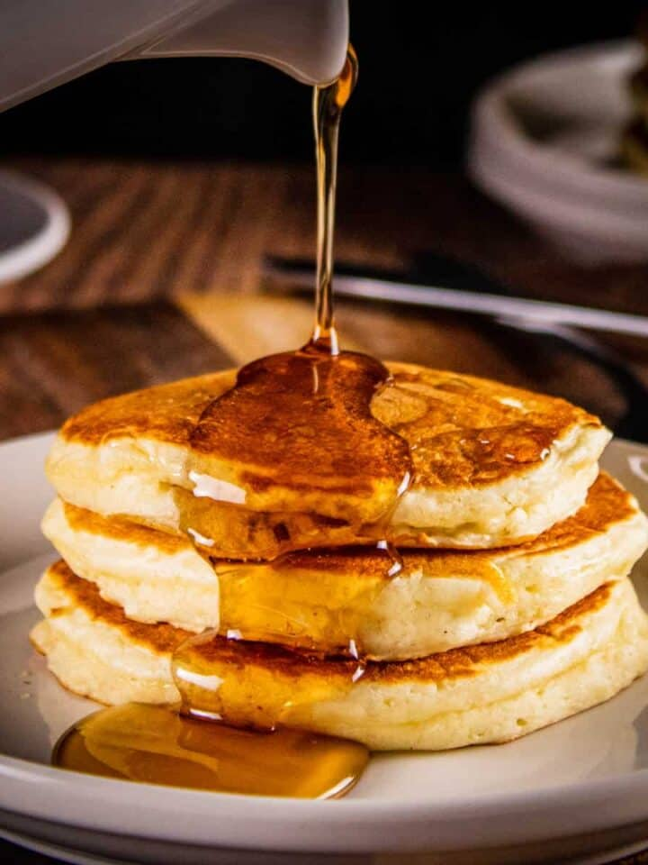 stack of pancakes with syrup pouring over them