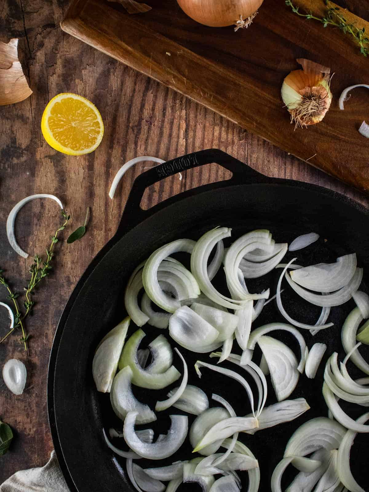 sliced onions in a cast iron skillet