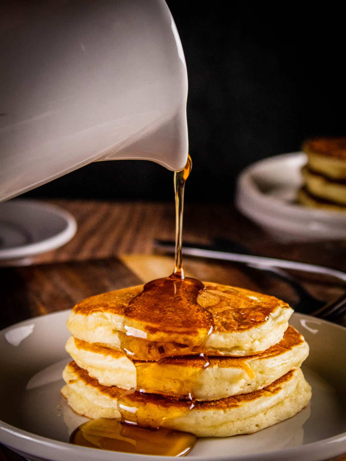 stack of pancakes with syrup pouring on them