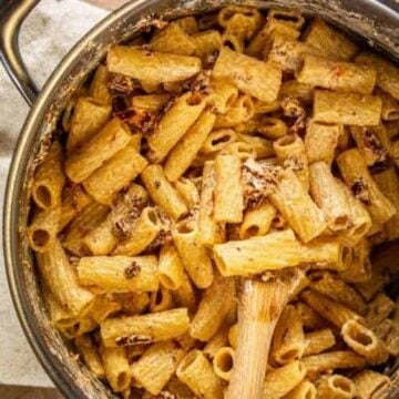 cooked rigatoni pasta in a large silver pot with goat cheese and sundried tomato sauce