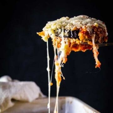 slice of eggplant parmesan above a white casserole dish with cheese stringing from it