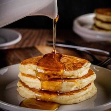 stack of three pancakes on a white with syrup being poured over the top of them