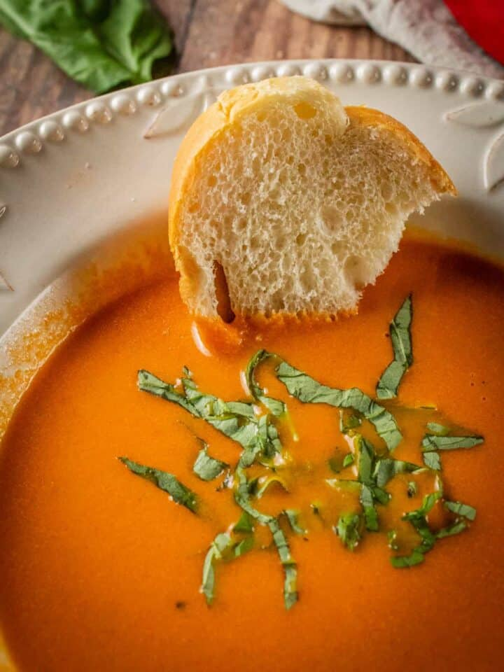 bowl of creamy tomato soup with fresh basil and a piece of bread
