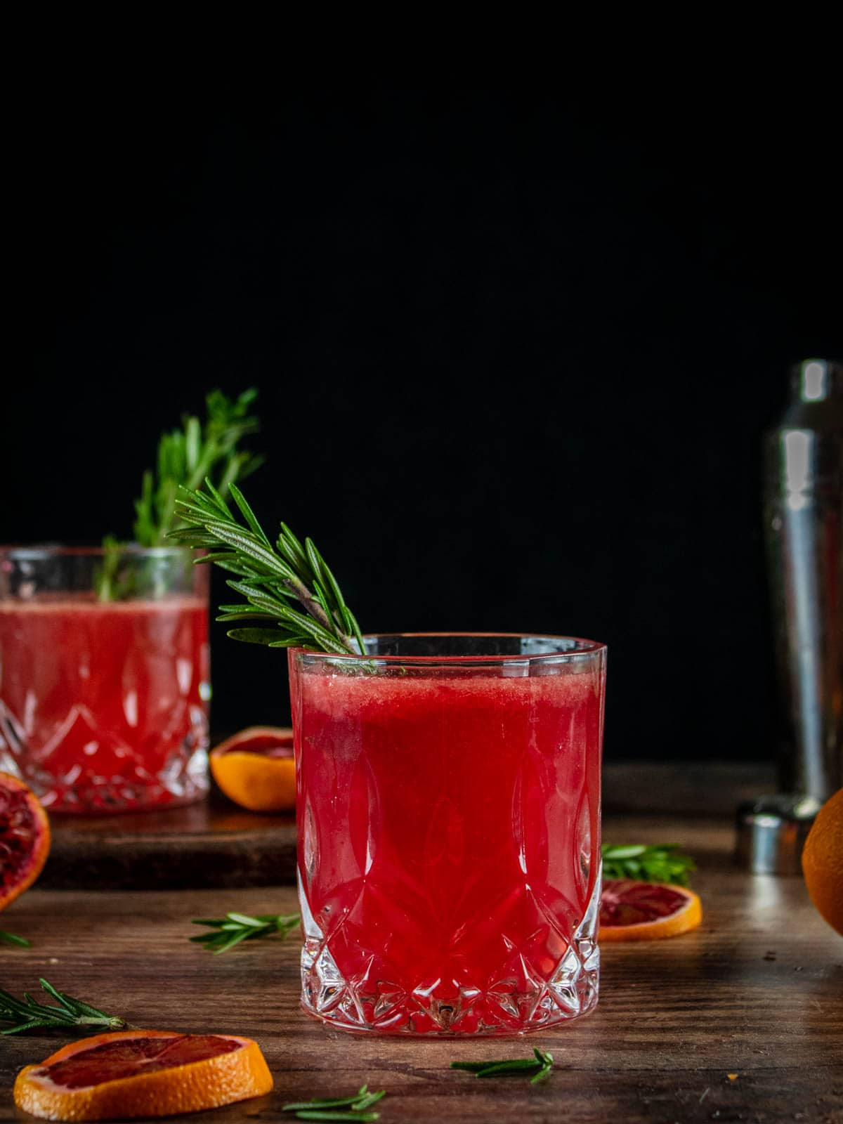 clear glasses with blood orange cocktail and rosemary garnish
