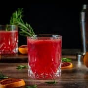 two whiskey glasses with blood orange cocktail garnished with fresh rosemary