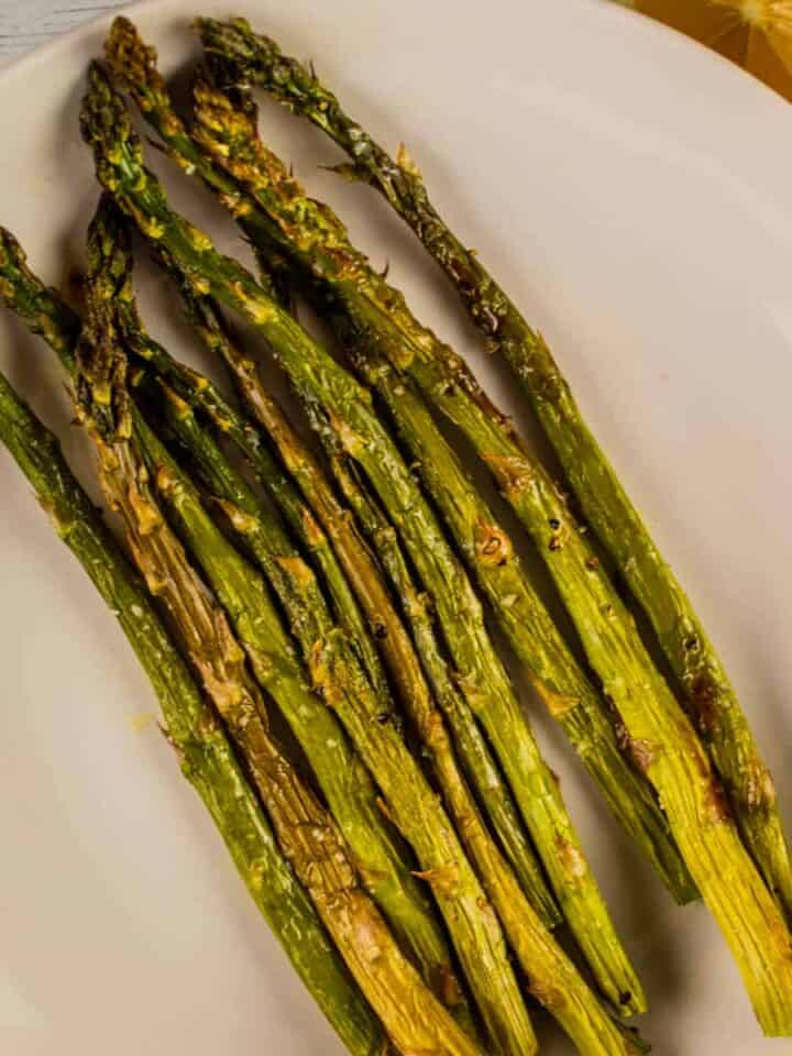 baked asparagus on a white plate