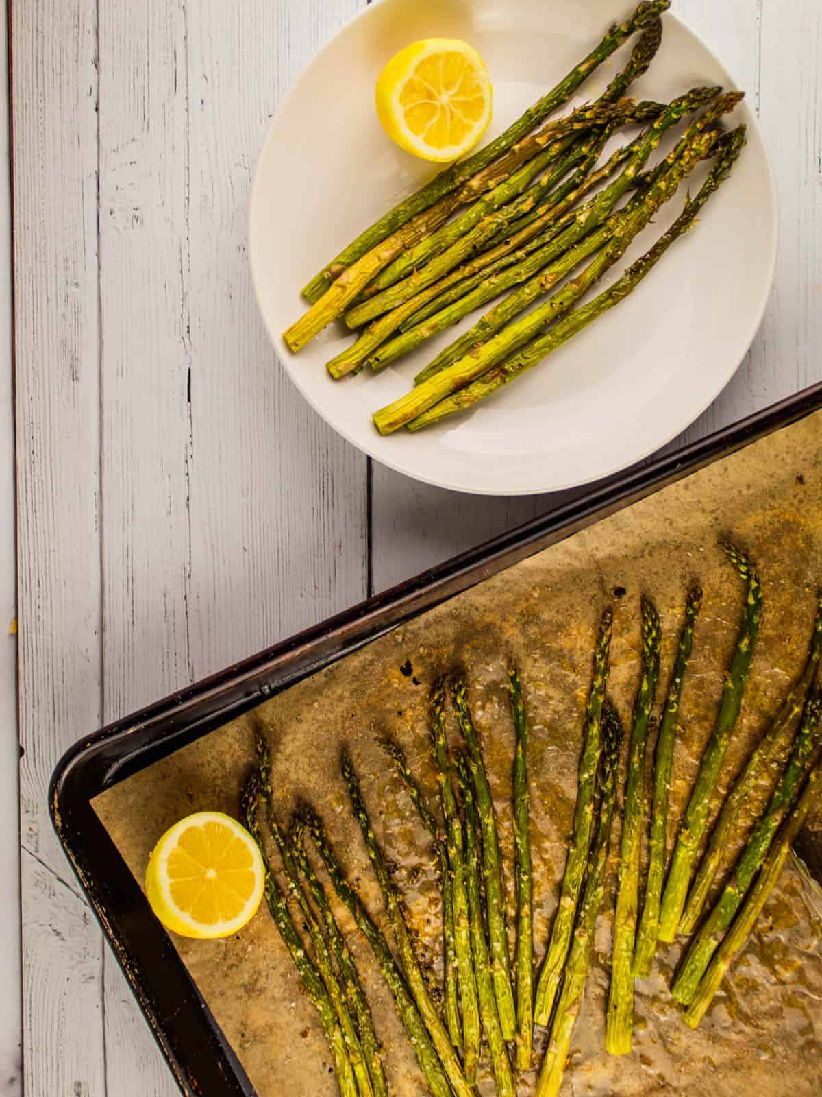 baked asparagus on a sheet pan and white plate with lemon