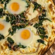 breakfast pizza with spinach, onion, ricotta and baked eggs