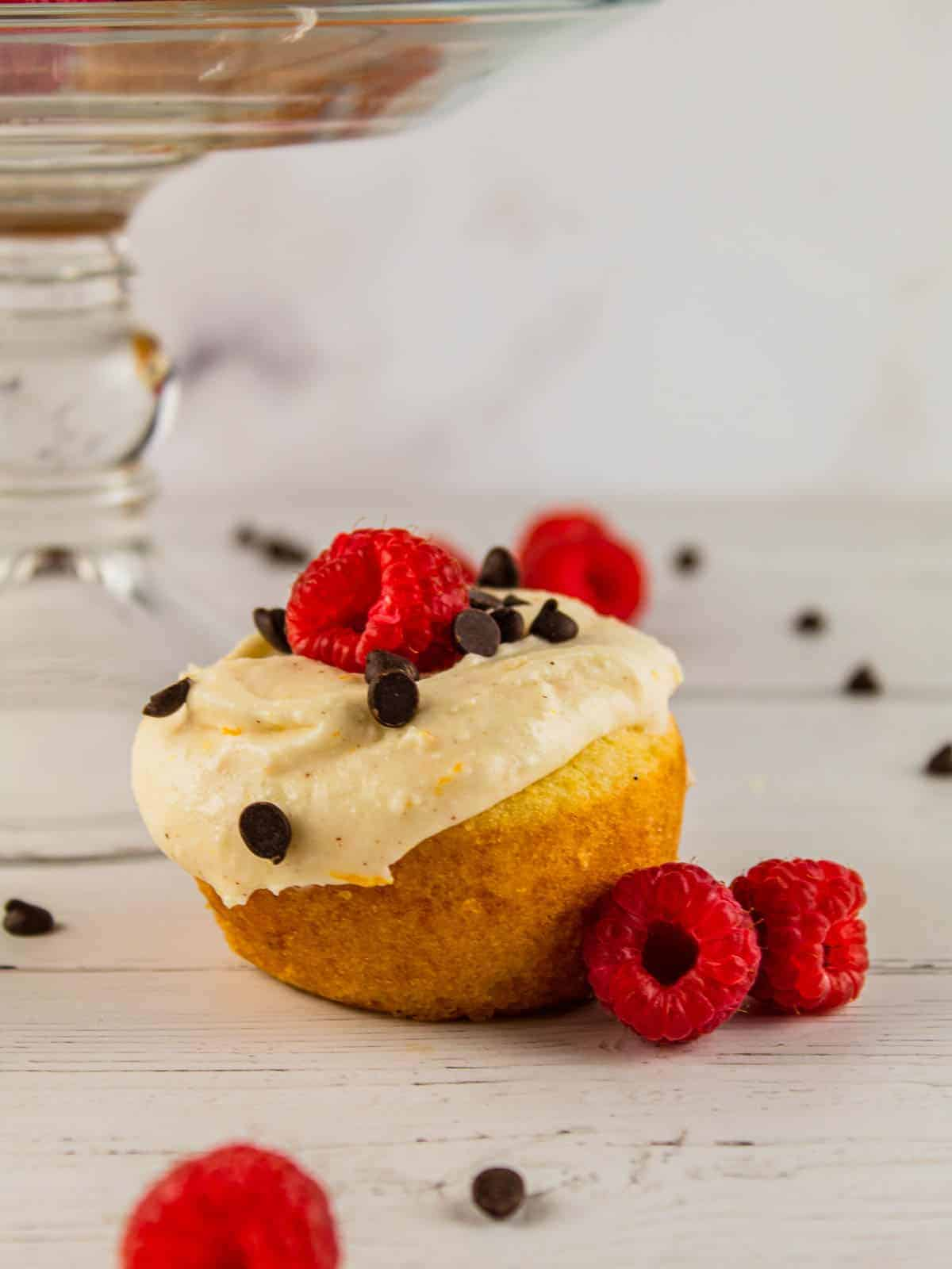 cannoli cupcake topped with fresh raspberry and mini chocolate chips