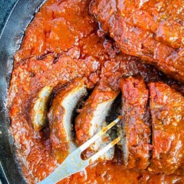 braised beef braciole in marinara with a serving fork