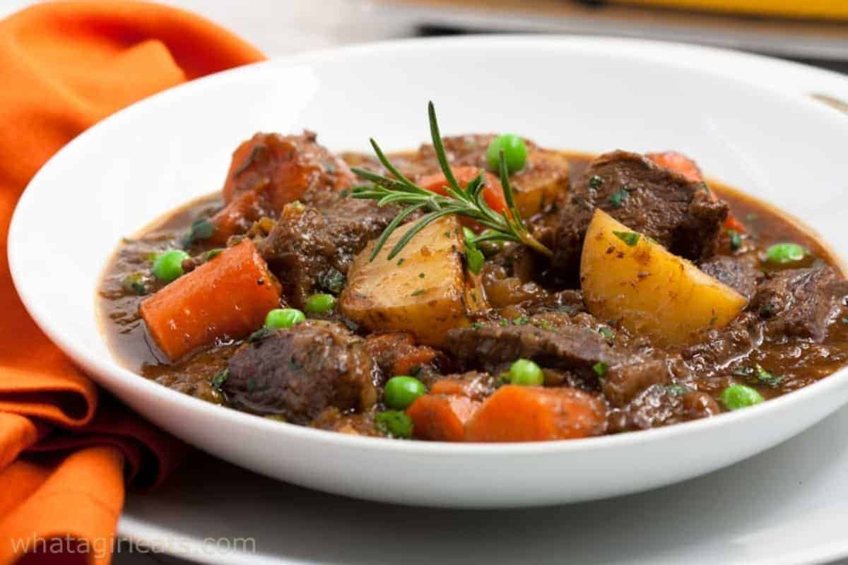 bowl of beef stew with carrots, peas and potatoes