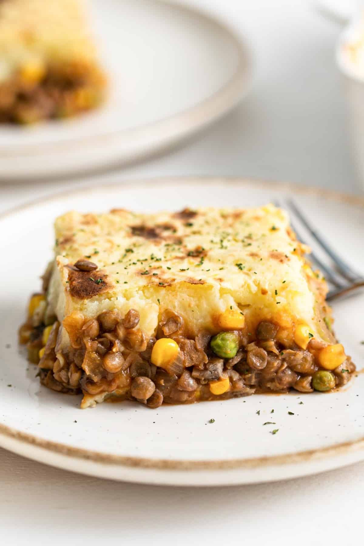 piece of lentil sheperds pie on a white plate