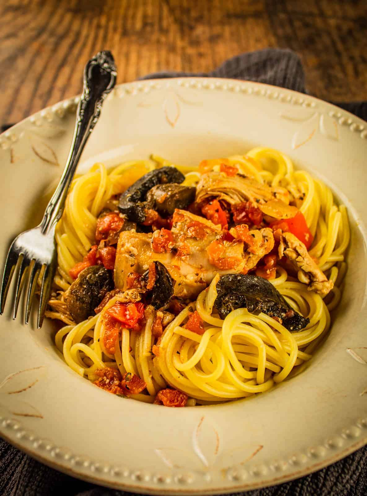 bowl of spaghetti topped with chicken cacciatore