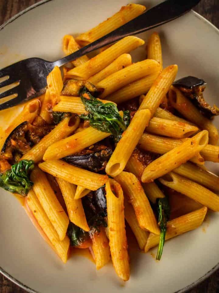 penne pasta on a plate with spinach and eggplant