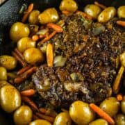 cooked pot roasted in a cast iron skillet with potatoes and carrots